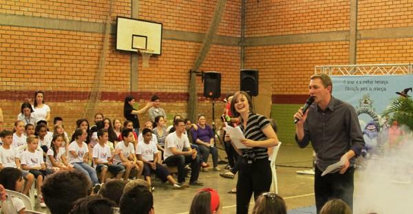 Os comunicadores Elizandra Gomes e Eduardo Cristofoli com alunos da escola municipal (Foto: Marcelo Borges/ Divulgação)