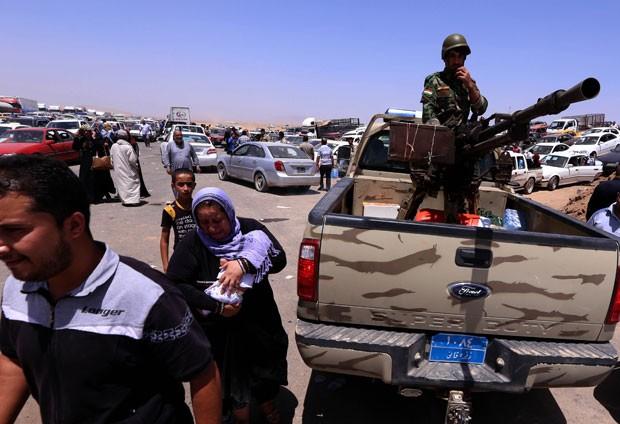 Famílias iraquianas fugindo da violência na província de Nínive se acumulam em posto de controle curso em Aski kalak nesta terça-feira (10) (Foto: Safin Hamed/AFP)