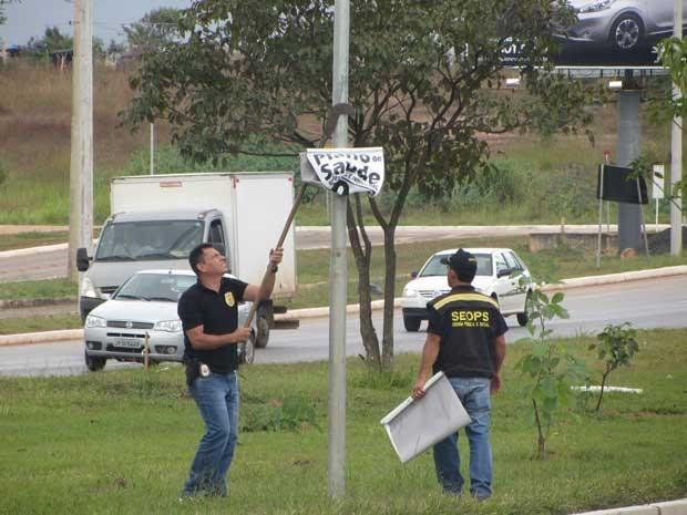 Fiscais retiram faixa pregada sem autorização em canteiro de via do DF (Foto: Aucilene Carvalho/Seops)