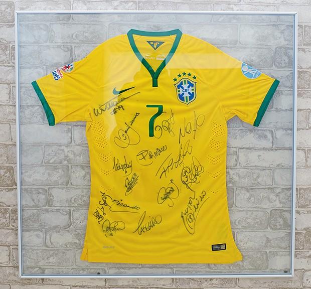 A camisa com autógrafos de jogadores da seleção foi presente do atacante Douglas Costa  (Foto:  )