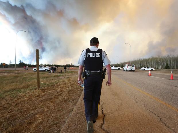 Policiais trabalham em bloqueio de estrada afetada pela fumaça de incêndio em Fort McMurray, em Alberta, no Canadá, na sexta (6) (Foto: Cole Burston/AFP)