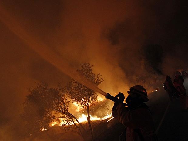 Bombeiro usa mangueira para combater fogo que avança sobre a vegetação perto de Los Angeles neste sábado (4) (Foto: Patrick T. Fallon/Reuters)