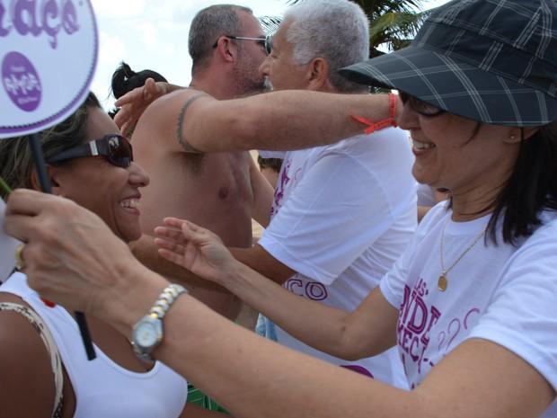 Grupo parou pessoas que passavam pela orla da praia de Tambaú para distribuir abraços (Foto: Walter Paparazzo/G1)