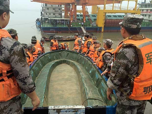 Equipes carregam um barco para resgate (Foto: Chen Zhuo / Reuters)