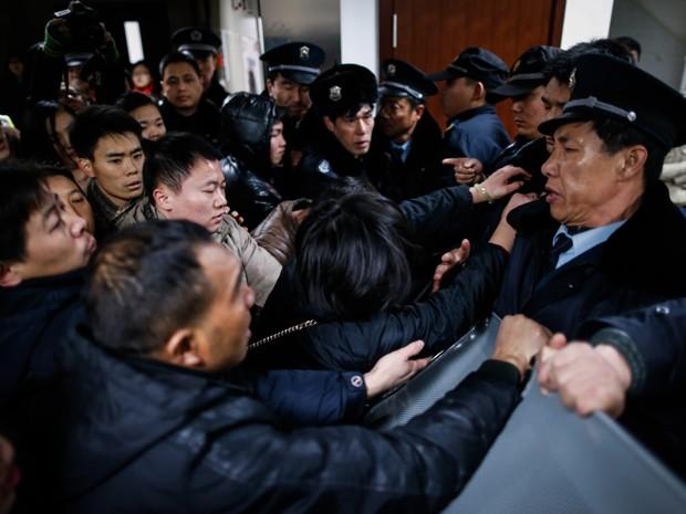 Parentes de vítimas entram em confronto com seguranças do hospital para onde foram levados feridos após tumulto em celebração de Ano Novo em Xangai, na China (Foto: STR/AFP)