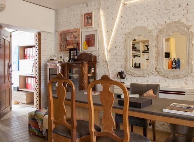 Na área interna, a parede de tijolinhos foi pintada de branco para ressaltar os móveis e objetos de madeira (Foto: J. Vilhora/Divulgação)