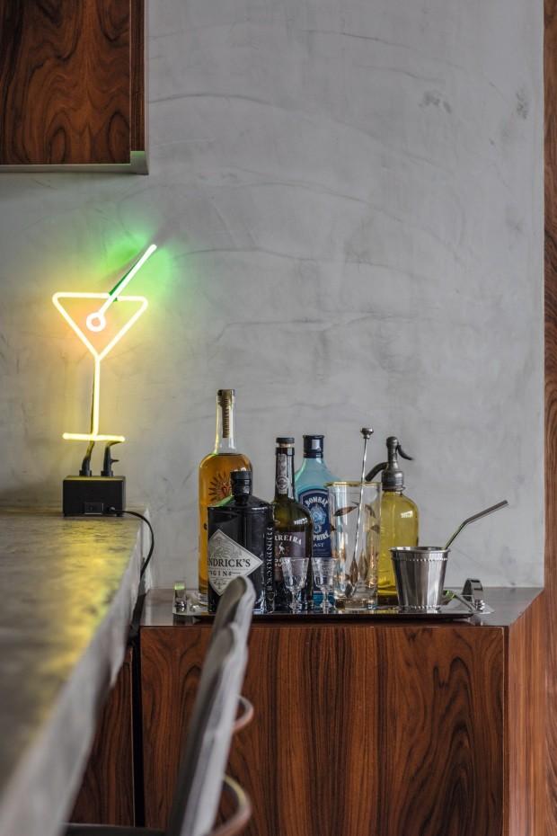 Bar. Em um canto da cozinha, um móvel de pau-ferro abriga garrafas de bebidas junto de uma luminária de néon (Foto: André Klotz / Editora Globo)