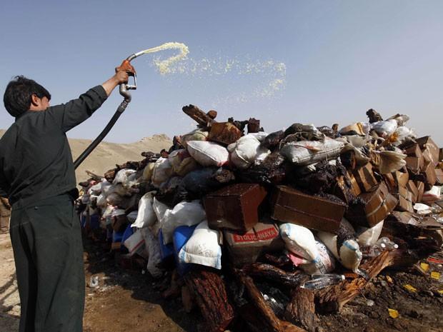 Trabalhador afegão se prepara para queimar uma pilha de drogas em Kabul, no Afeganistão, neste domingo (14). As cerca de 25 toneladas de drogas foram apreendidas nos últimos nove meses. Entre o material apreendido estão 1,8 toneladas de heroína, 2,8 toneladas de ópio e 140 kg de haxixe. Foram presos 907 suspeitos. (Foto: Omar Sobhani/Reuters )