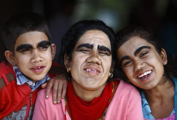 Devi e seus dois filhos posam para foto após terem comoeçado o tratamento a laser com o objetivo de diminuir os pelos da face. (Foto: Reuters/Navesh Chitrakar)