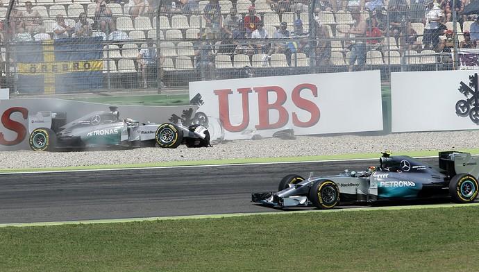 Nico Rosberg passa pelo carro de Lewis Hamilton batido no treino classificatório para o GP da Alemanha (Foto: AP)