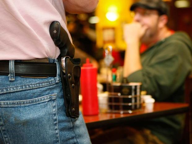 Bryan Hull, diretor de associação que defende o porte aberto de armas, mostra arma durante reunião na cidade em foto de novembro de 2012 (Foto: REUTERS/Bill Waugh/Files)