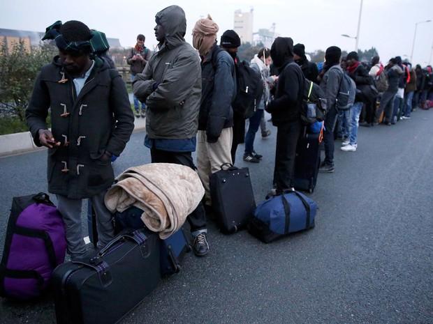 Migrantes fazem fila nesta segunda-feira (24) para aguardar a transferência do acampamento de Calais, no norte da França, para centros de acolhida espalhados pelo país (Foto: Neil Hall/ Reuters)