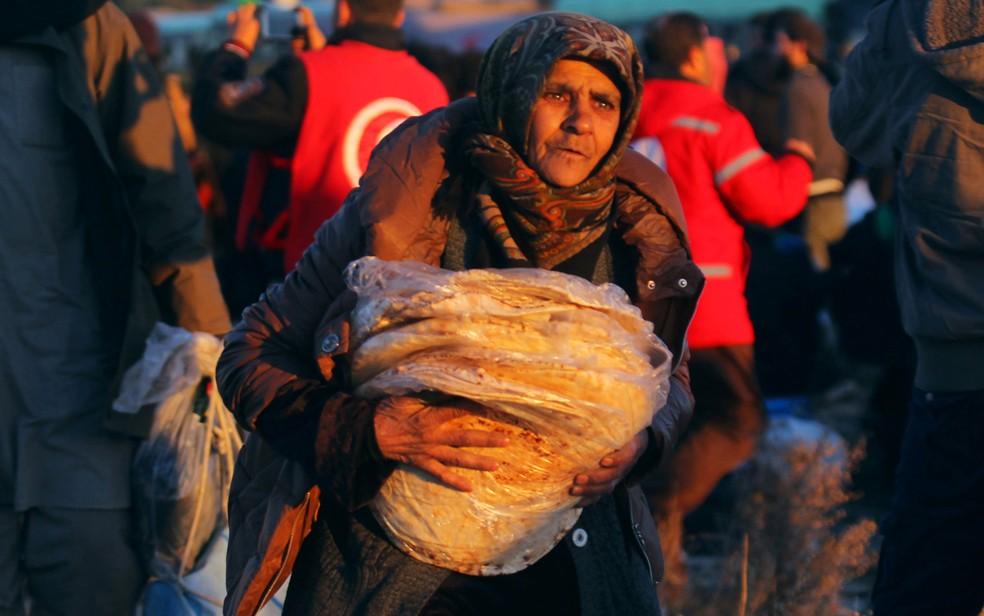 Mulher carrega alimento na chegada a al-Rashideen, depois de ser retirada de Aleppo, na Síria, na quinta (15) (Foto: Reuters/Ammar Abdullah)