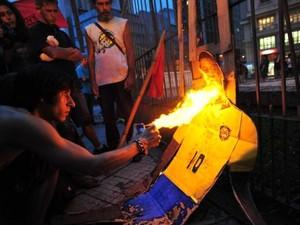 Em protesto, manifestantes tentam colocar fogo em boneco do Pelé (Foto: Carlos Macedo / Agência RBS)