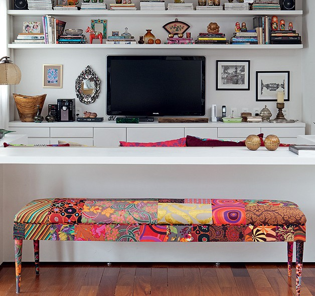 Nas costas do sofá da sala de televisão, bancada de trabalho projetada por Maristela Gorayeb e banco Or, todo de patchwork, de Ana Morelli