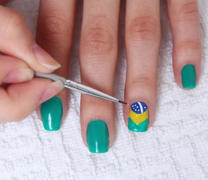 Com o pincel fininho nº000 e o esmalte branco faça um risco fino no meio da bola azul e alguns pontinhos para simbolizar a faixa e as estrelas da bandeira do Brasil (Foto: Arquivo pessoal)