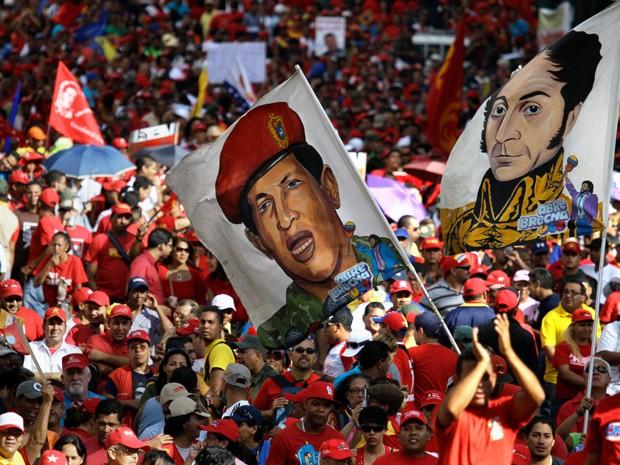 Nesta foto de 10 de janeiro, militantes do presidente da Venezuela Hugo Chávez carregam bandeiras com o desenho do presidente com vestimentas militares e com a imagem de Simon Bolivar durante a posse simbólica de Chávez, em Caracas (Foto: AP Photo/Fernando Llano, File)