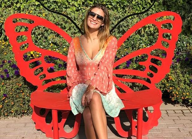 Luma, filha de Elaine e César, posa em banco em formato de borboleta no Dubai Miracle Garden (Foto: Reprodução/Instagram)