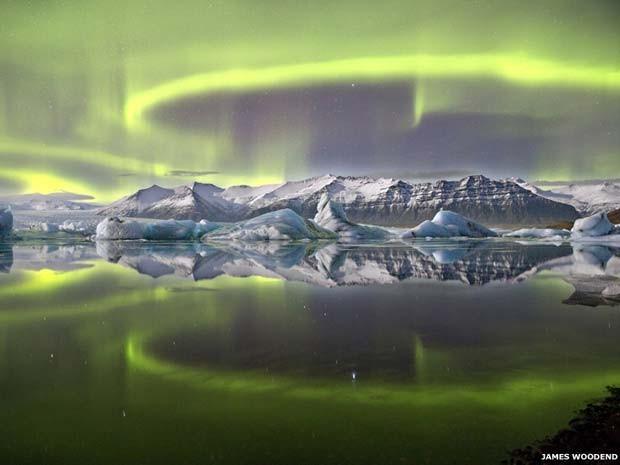 A aurora verde e vívida que cruza o céu noturno islandês é refletida na lagoa glacial de Vatnajökull, no Parque Nacional Jökulsarlon; a imagem tirada pelo fotógrafo britânico James Woodend ganhou o prêmio de Fotógrafo da Astronomia de 2014 (Foto: James Woodend)