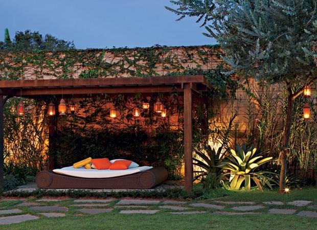 Além das lanternas com velas penduradas no pergolado, este jardim do Espaço Til (SP) tem spots de alumínio dispostos no chão com foco voltado para a estrutura. Para isso, é necessária a instalação elétrica prévia para lâmpadas de, no mínimo, 50 W. Em meio à vegetação, as mesmas luminárias, da Luxsim, empregadas pela arquiteta Patrícia Perna, têm outra função: revelar a beleza da orquídea-bambu ao fundo. Projeto de execução da paisagista Mariana de Castilho Barbosa. (Foto: Evelyn Müller/Editora Globo)