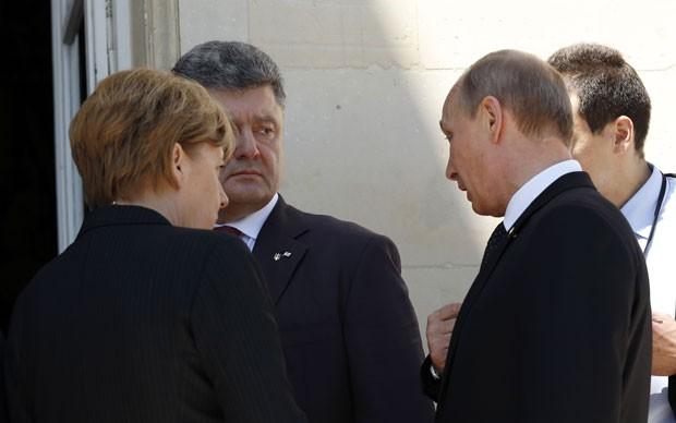 O presidente da Rússia, Vladimir Putin, e o presidente eleito da Ucrânia, Petro Poroshenko, conversam na presença da chanceler alemã, Angela Merkel, em encontro durante a celebração do aniversário de 70 anos do Dia D na França nesta sexta-feira (6) (Foto:  Kevin Lamarque/Reuters)