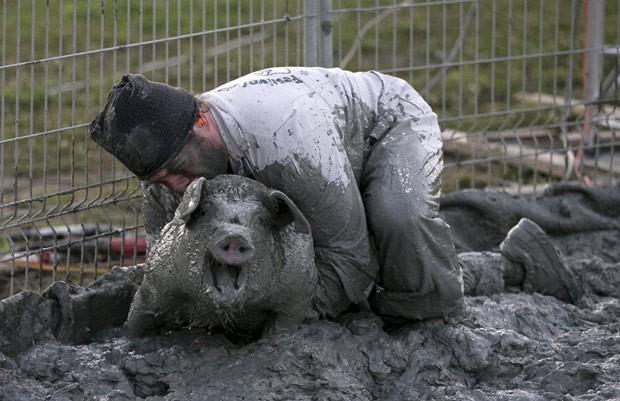 Participantes tinham que capturar um porco na lama (Foto: Christinne Muschi/Reuters)