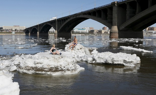 Russos tomam banho de sol deitados sobre blocos de gelo na Sibéria (Foto: Ilya Naymushin/Reuters)