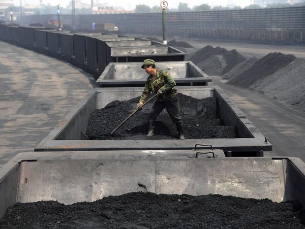 Imagem de julho de 2013 mostra trabalhador em carga de carvão transportada por trem na região de Shanxi, na China. País asiático, EUA e Índia aumentaram emissões de CO2 em 2013, segundo estudo (Foto: Arquivo/AP)