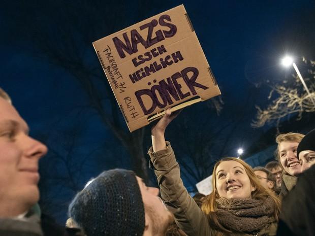 Uma mulher segura um cartaz com a frase 'Nazistas comem Kebab Doner clandestinamente' em protesto contra uma marcha anti-islamismo do grupo 'Europeus Patrióticos contra a Islamização do Ocidente' em Colônia, na Alemanha (Foto: Maja Hitij/DPA/AFP)