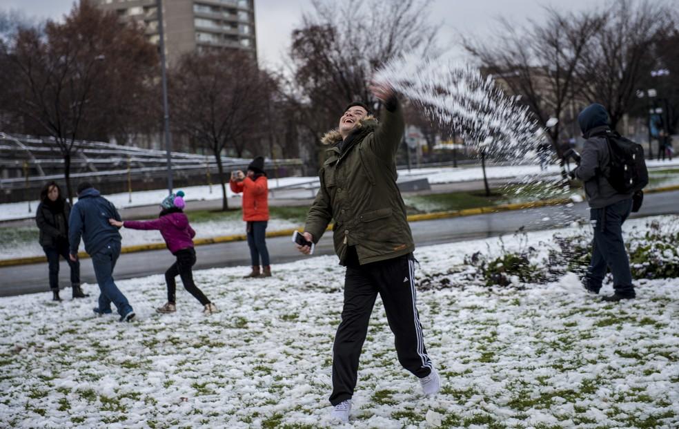 Pessoas brincam com a neve em Santiago neste sábado (15) (Foto: Martin Bernetti/ AFP)