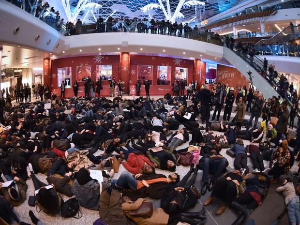 Grupo de manifestantes se deita em shopping de Londres para apoiar os protestos contra morte de negros por policiais brancos dos EUA (Foto: LEON NEAL/AFP)