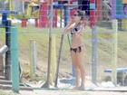 Bianca Bin se refresca com banho de mangueira na praia