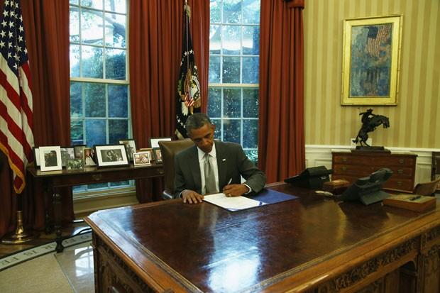 O presidente dos EUA, Barack Obama, assina lei que permite aporte de US$ 225 milhões para sistema antimísseis de Israel nesta segunda-feira (4) na Casa Branca  (Foto: Mark Wilson/Getty Images/AFP )