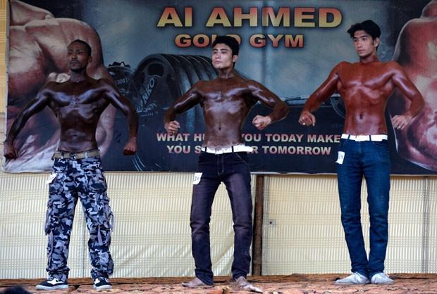 Três atletas exageram na pintura para divulgar campeonato de fisiculturismo no Paquistão (Foto: Akhtar Soomro/Reuters)