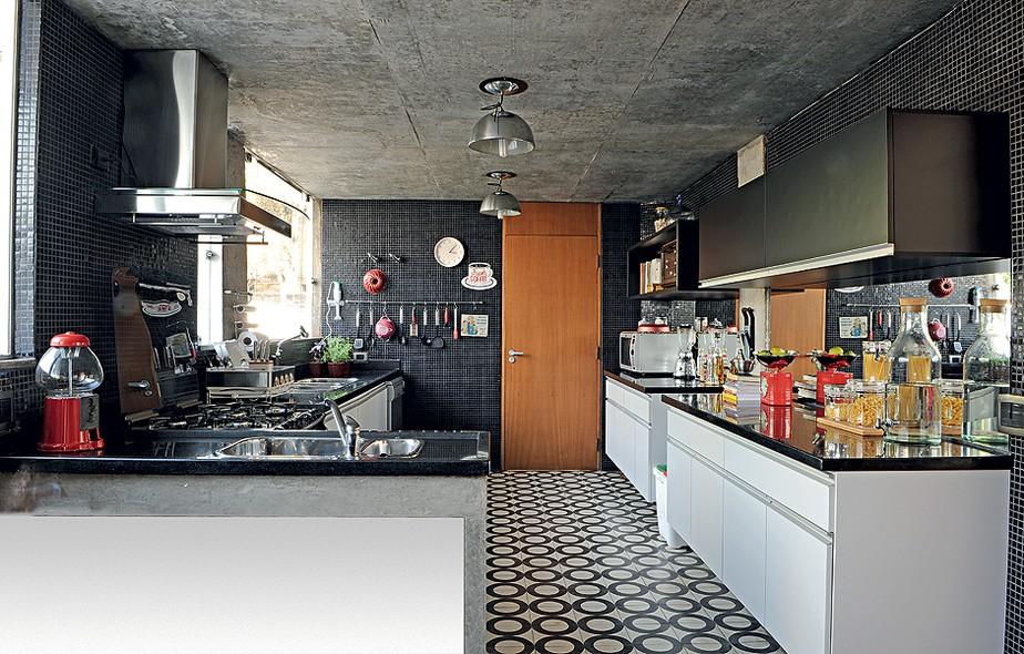Nada comum em cozinhas, o espelho entre os armários reflete a luz que entra pelas grandes janelas – ideia da cenógrafa Claudia Terçarolli. As pastilhas de vidro pretas foram escolhidas pela facilidade de limpar