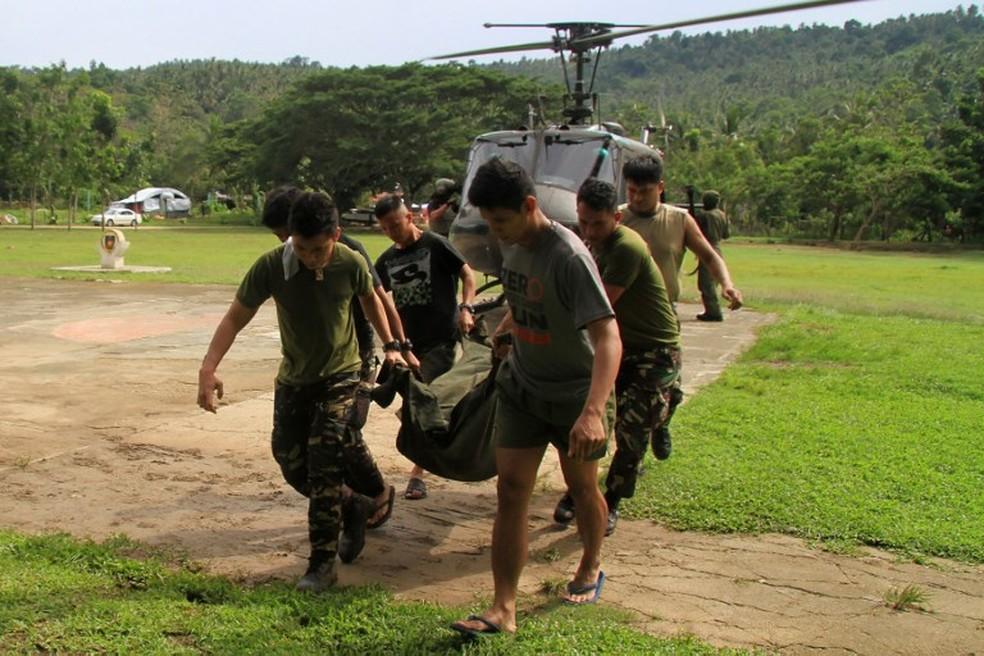 Soldados carregam corpo de colega morto durante combates entre forças estatais e Estado Islâmico, no sul das Filipinas (Foto: RICHELE UMEL / AFP)
