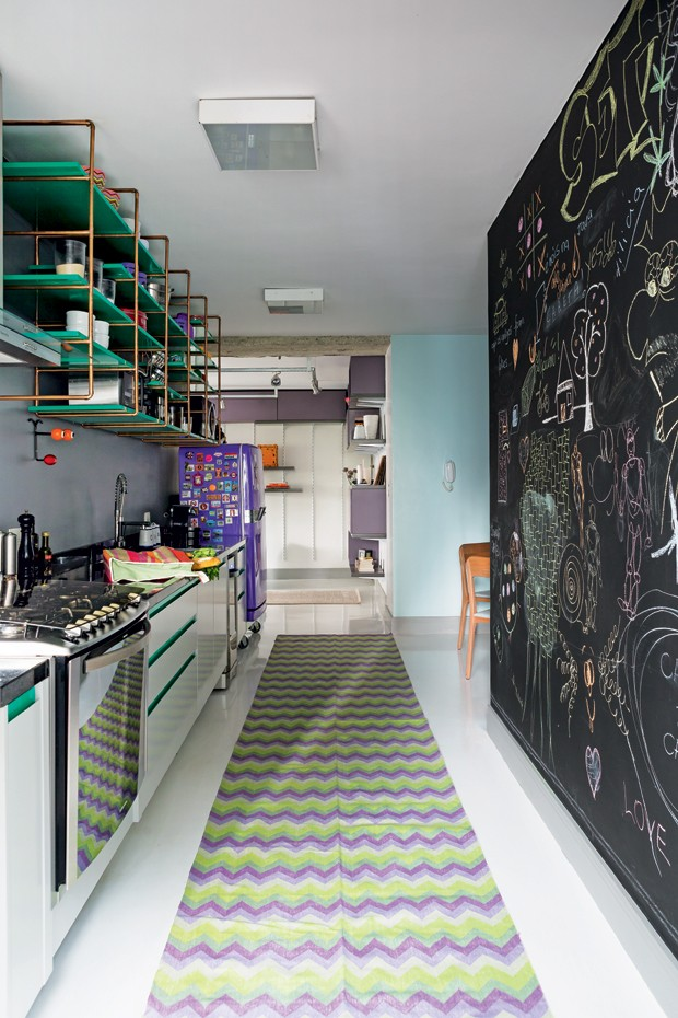 Desenhos de giz na grande parede, pintada com tinta lousa, alegram a cozinha, onde outro destaque é uma antiga geladeira que ganhou pintura em tons de roxo. Passadeira da Square Foot (Foto: Edu Castello/Editora Globo)
