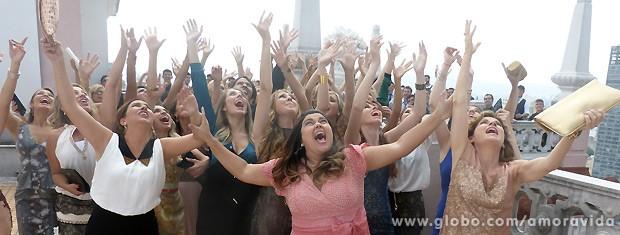 Perséfone e as outras convidadas tentam agarrar o buquê, mas ele voa longe (Foto: Amor à Vida / TV Globo)