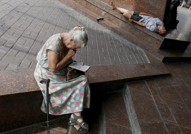 Mulher idosa faz palavras cruzadas em uma praça de Kiev, na Ucrânia, em foto de 20 de julho: segundo pesquisas, mulheres com falhas cognitivas leves sucumbem à demência mais rapidamente do que homens (Foto:  Reuters/Gleb Garanich  )