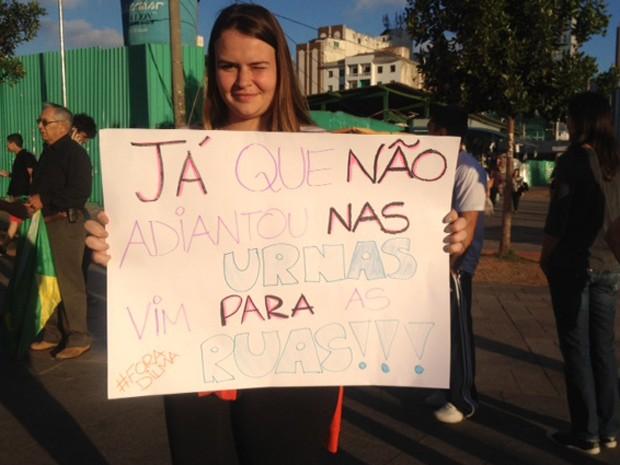 A estudante Nathaly Hackradt, de 19 anos, segura uma faixa de protesto  (Foto: Roney Domingos/G1)