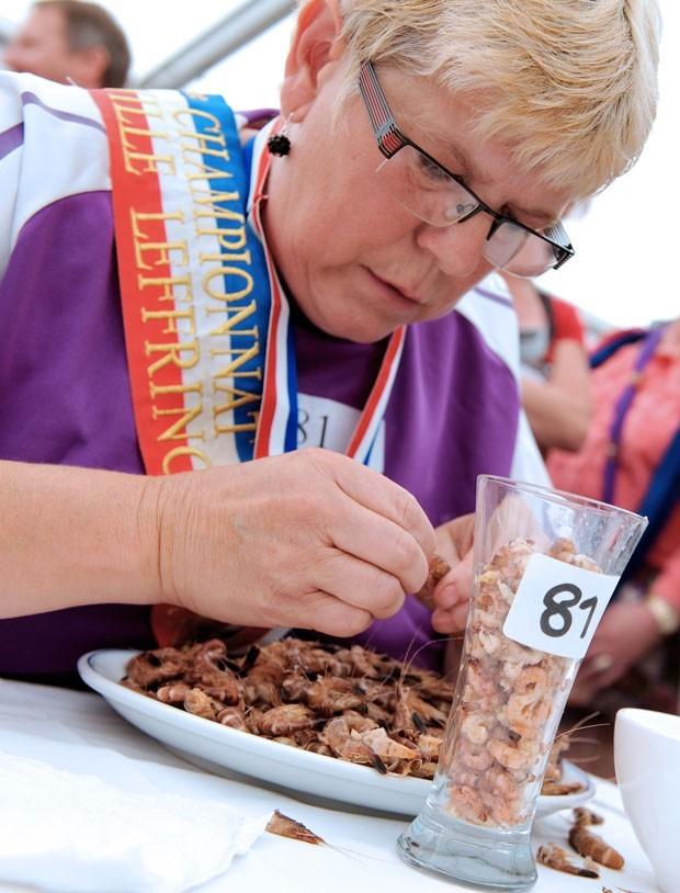 No dia 5 de agosto, a francesa Colette Vanzinghel venceu uma competição de descascar camarão em Leffrinckoucke, na França. Ela levou a sexta edição do concurso ao descascar 150 gramas de camarões em dez minutos.  (Foto: Philippe Huguen/AFP)