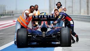 Carro de Sebastian Vettel é empurrado de volta aos boxes (Foto: AFP)