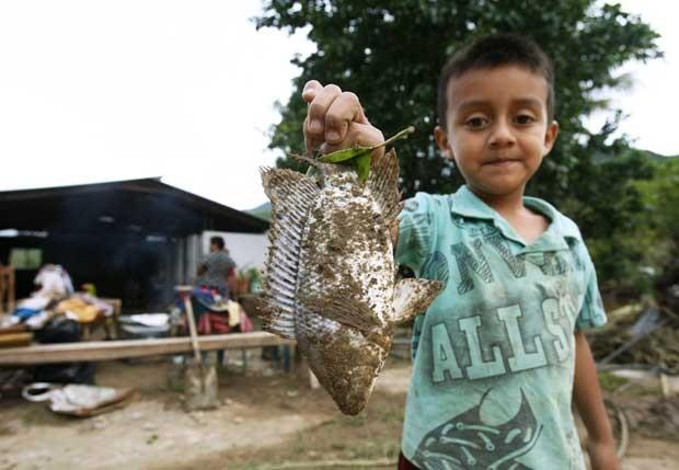 Luis segura um peixe morto que encontrou no pátio de sua casa em San Cristobal Sola de Vega (Foto: Jorge Luis Plata/ Reuters)