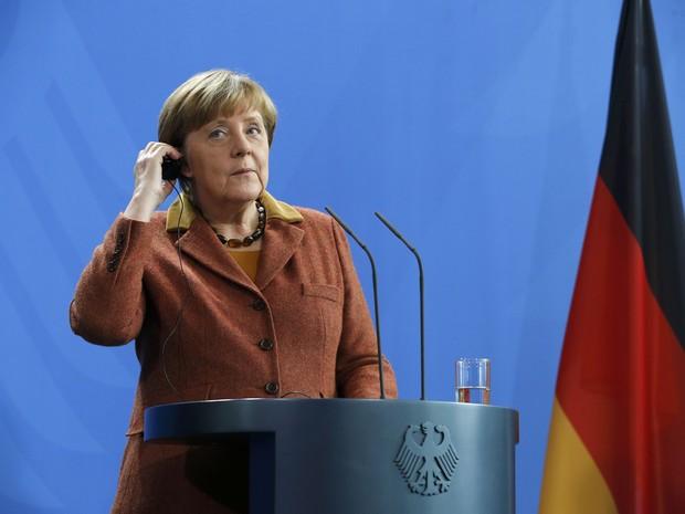 Angela Merkel ajusta fone de ouvido durante conferência em Berlim na sexta-feira (5) (Foto: Fabrizio Bensch/Reuters)