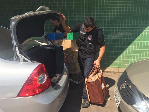 Policial retira malote com material apreendido durante operação nesta quinta-feira (1º) para apurar máfia de órteses e próteses (Foto: Alexandre Bastos/G1)