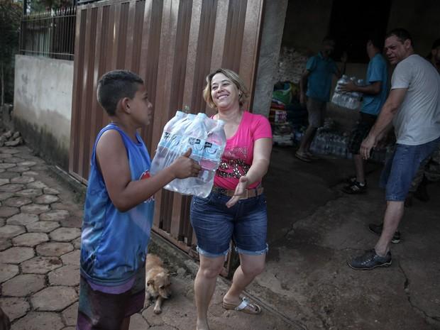 'Família do Barulho' entrega doação de água em Gesteira, na zona rural de Barra Longa. Moradores ajudaram no descarregamento em um bar, cujo dono se comprometeu a ajudar na distribuição (Foto: Fábio Tito/G1)