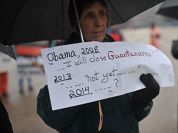 Mulher segura cartaz em que lembra promessa de 2008 feita pelo presidente Obama (Foto: Nicholas Kamm/AFP)