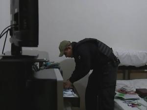 Policial procura por material em casa de suspeito na região de Araçatuba (Foto: Reprodução / TV TEM)