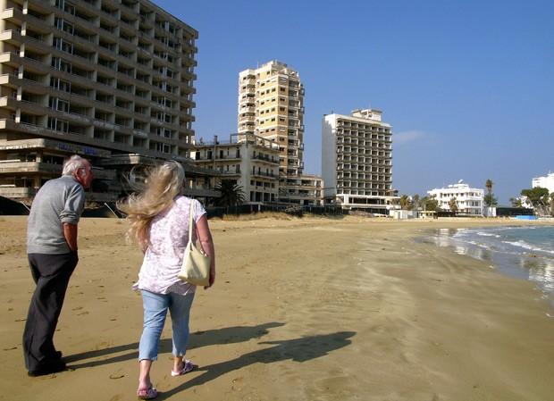 Casal caminha pela praia deserta em Varosha em 17 de janeiro (Foto: AP Photo/Petros Karadjias)