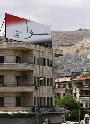 """Cartaz eleitoral com a assinatura do presidente Bashar al-Assad e a palavra """"juntos"""", na capital Damasco. Campanha para eleições do dia 3 de junho começaram neste domingo (11) (Foto: Louai Beshara / AFP)"""